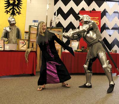 """Roger McKinney, from Shelby, Ohio, with the help of seventh grader Chelsey Williams (left) demonstrate the use of a coif (or chainmail hood,) worn in the middle ages. Before the demonstration began, Roger asked, """"Is it ok to do something scary with you?"""""""